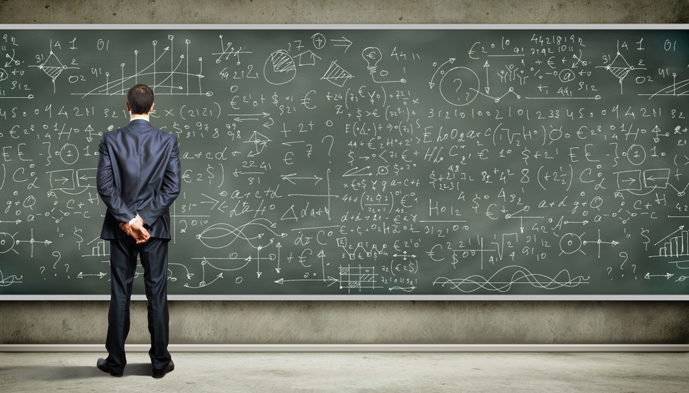 Business person standing against the blackboard with a lot of data written on it.jpeg