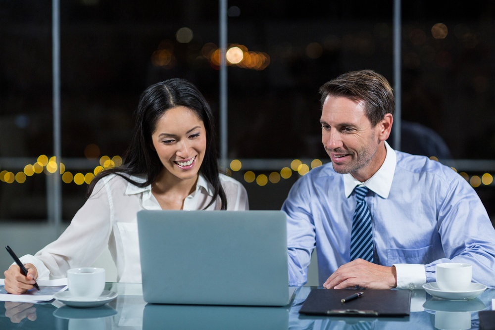 Businessman discussing with colleague over laptop in the office.jpeg