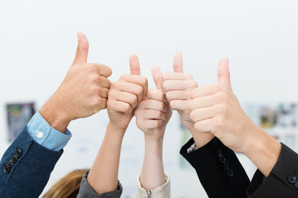 Successful diverse young business team giving a victorious thumbs up to show their success and motivation, close up view of their raised hands.jpeg