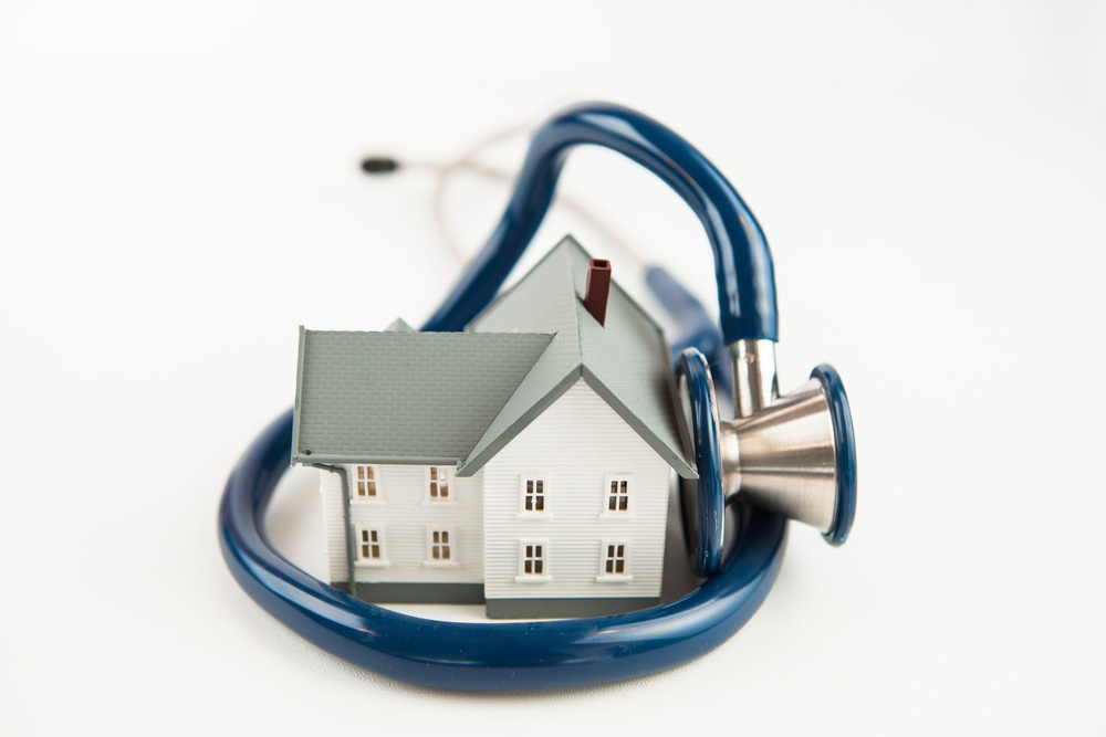 Blue stethoscope wrapped aroud tiny house model on white background.jpeg