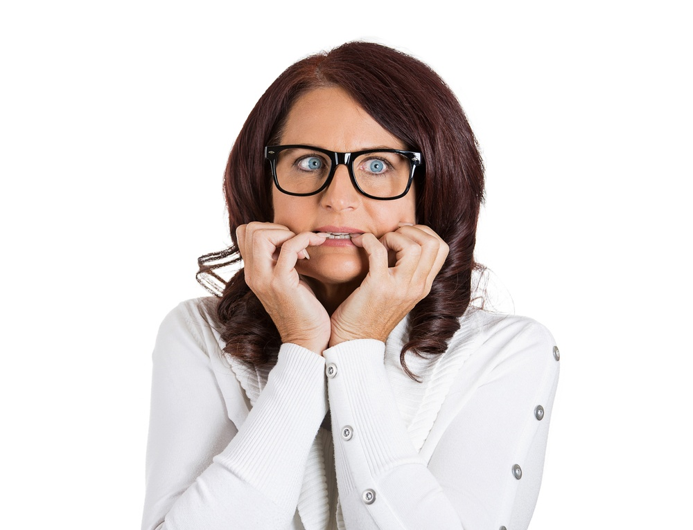 Closeup headshot portrait unhappy scared anxious woman with glasses. Female biting nails looking with craving, envy for something worried isolated on white background. Human face expression emotions